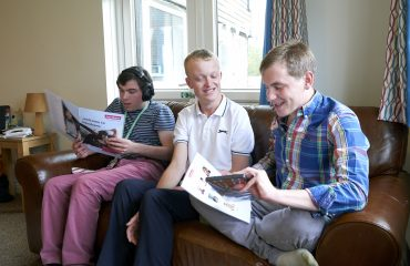 Three young men sitting on a sofa, reading and chatting.