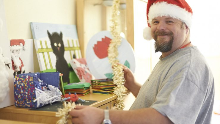 John wearing a Santa hat, smiling at the camera and decorating his house with Christmas decorations.