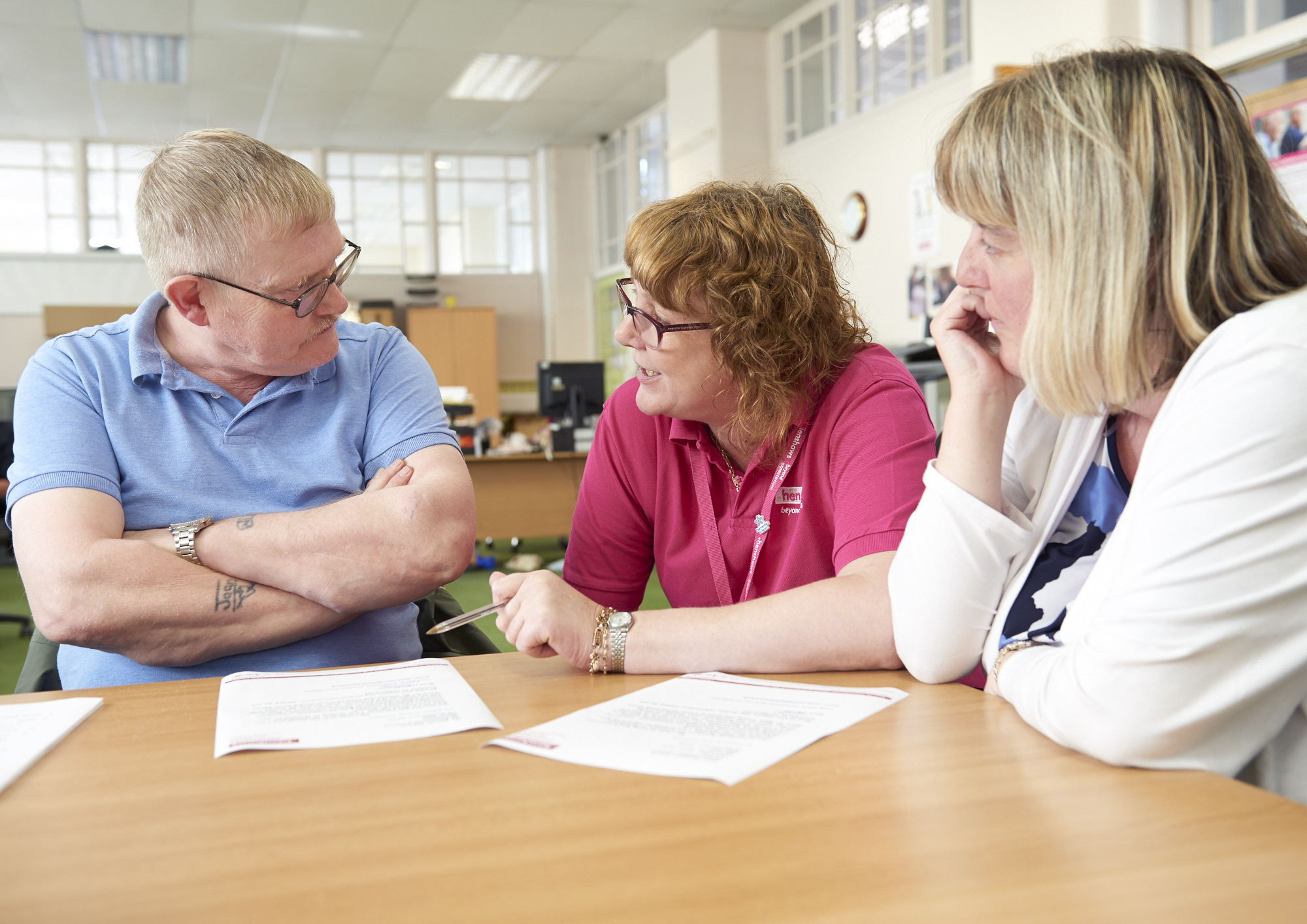 Philippa from the centre chatting to two service users around a table.