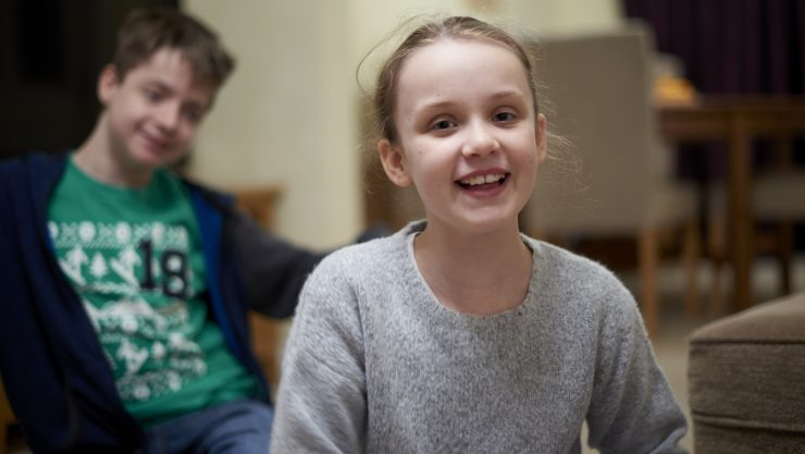 A young girl sat close to the camera smiling, whilst her older brother sits smiling in the background.