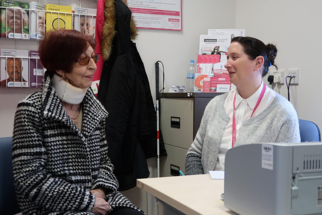 Woman with red hair sitting and talking to Gail, our Patient Support Officer