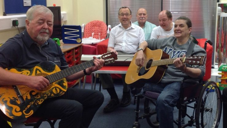 The guitar group in Liverpool sitting around a table and holding their instruments