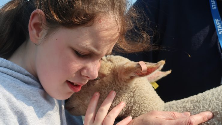 Image shows young girl with eyes closed, holding a lamb in her hands