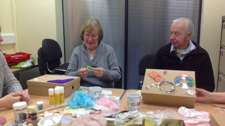 A couple creating sensory 'memory boxes' in a Memory Lane group session.