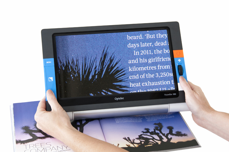 A digital magnifier over a magazine, showing the text magnified on the screen.