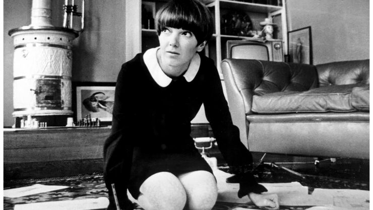 Black and white photo of Mary Quant, kneeling on the floor in a living room with paper work around her.
