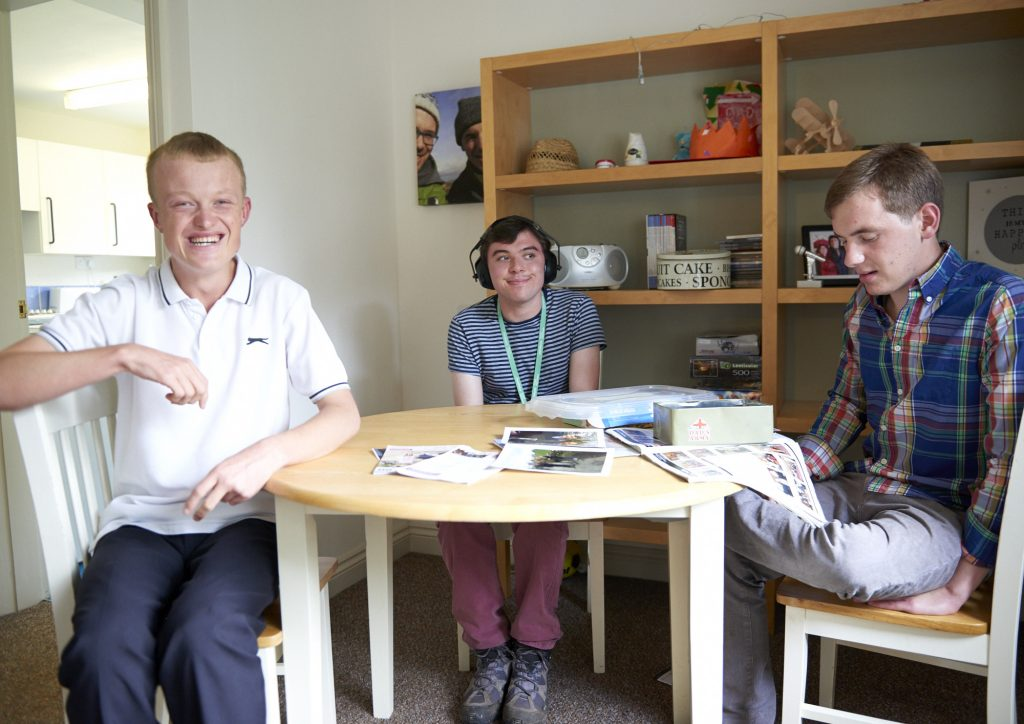 Three young tenants sat around a shared table in a Henshaws Supported house