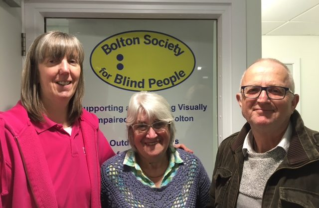 Image of Julie from Henshaws, stood next to BSBP volunteer Dorothy Mercer, and BSBP member Dave Mulligan, in front of the BSBP logo.