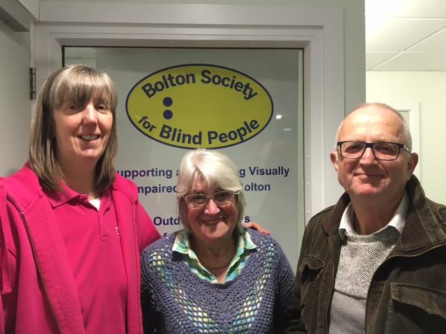 Image of Julie from Henshaws, stood next to BSBP volunteer Dorothy Mercer, and BSBP member Dave Mulligan, in front of the BSBP logo.
