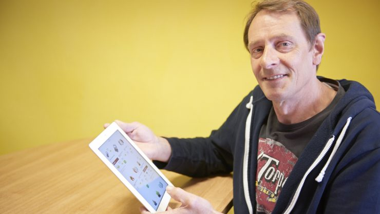 Man sitting at a table holding an iPad, looking up at the camera.