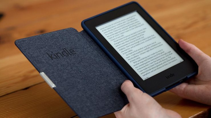 Image of a Kindle, in a case that's opened up like a book, being held in someone's hands.