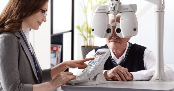 An image of an elderly gentleman having his eyes examined at home, with a female optician guiding his test on an tablet.