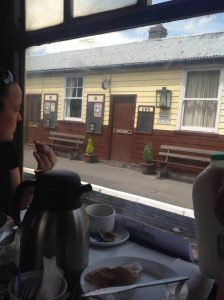 A photo taken from the window of the train as it passes by an old station, with someone eating afternoon tea in the corner of the image