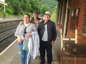 3 service users at the station platform, smiling at the camera