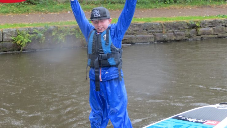 Young boy standing in a kayak and triumphantly holding the paddle in the air.