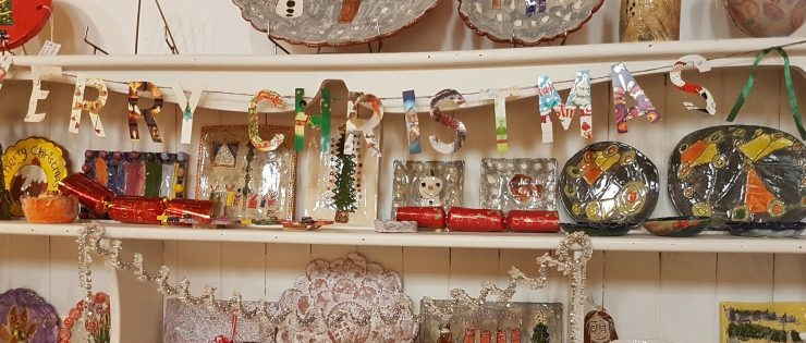 A shelf of crafts with the word Merry Christmas in paper bunting.