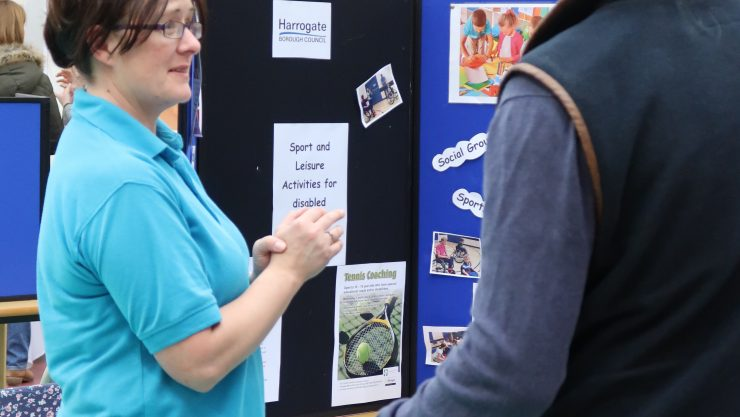 An exhibitor at the fair talking to parents visiting the event.