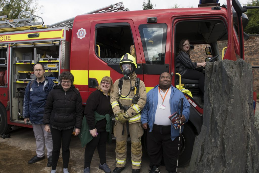 Art Makers with a fireman in front of a fire engine.