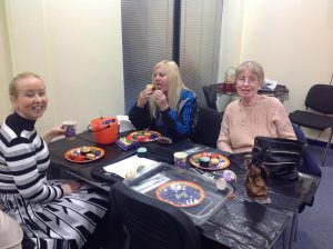 Three women sat at a table. Pumpkin buckets and plates full of sweets sit on the table.