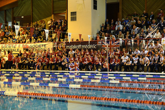 A crowd od people cheering at the side of a swimming pool