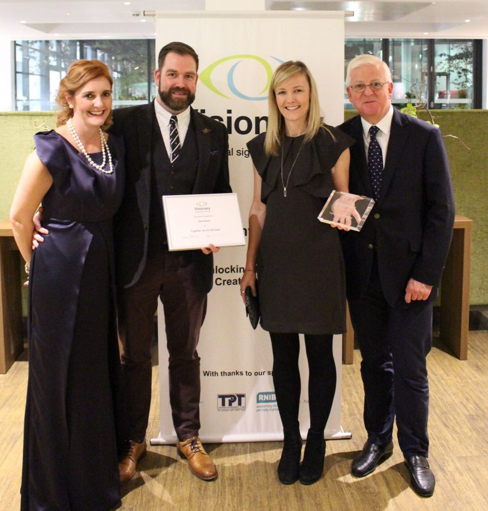 Four well dressed people,with Rob and Fiona holding the award in the centre, in front of a Visionary banner