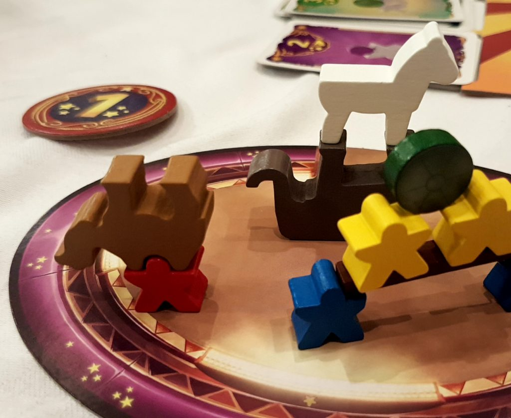 Circular board game with stars around the edge and different shaped wooden blocks stacked against each other.