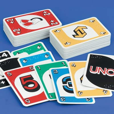 A deck of Uno cards spread across a table with braille numbers in the corners.