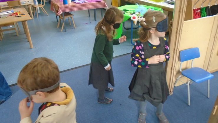 Three primary school children wearing blindfolds to help understand what sight loss is like.