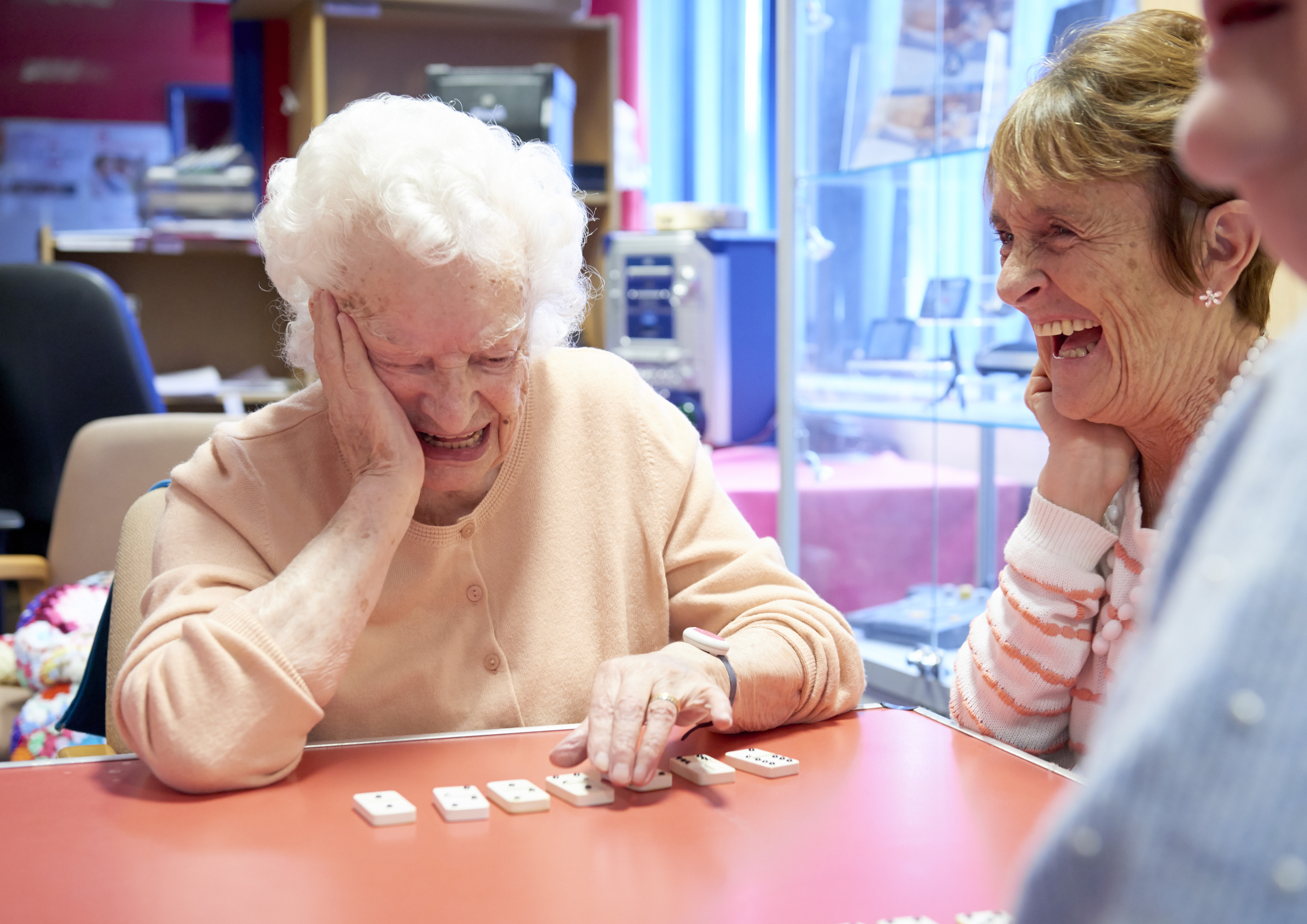 Two women laughing as they play dominoes in the Trafford hub.