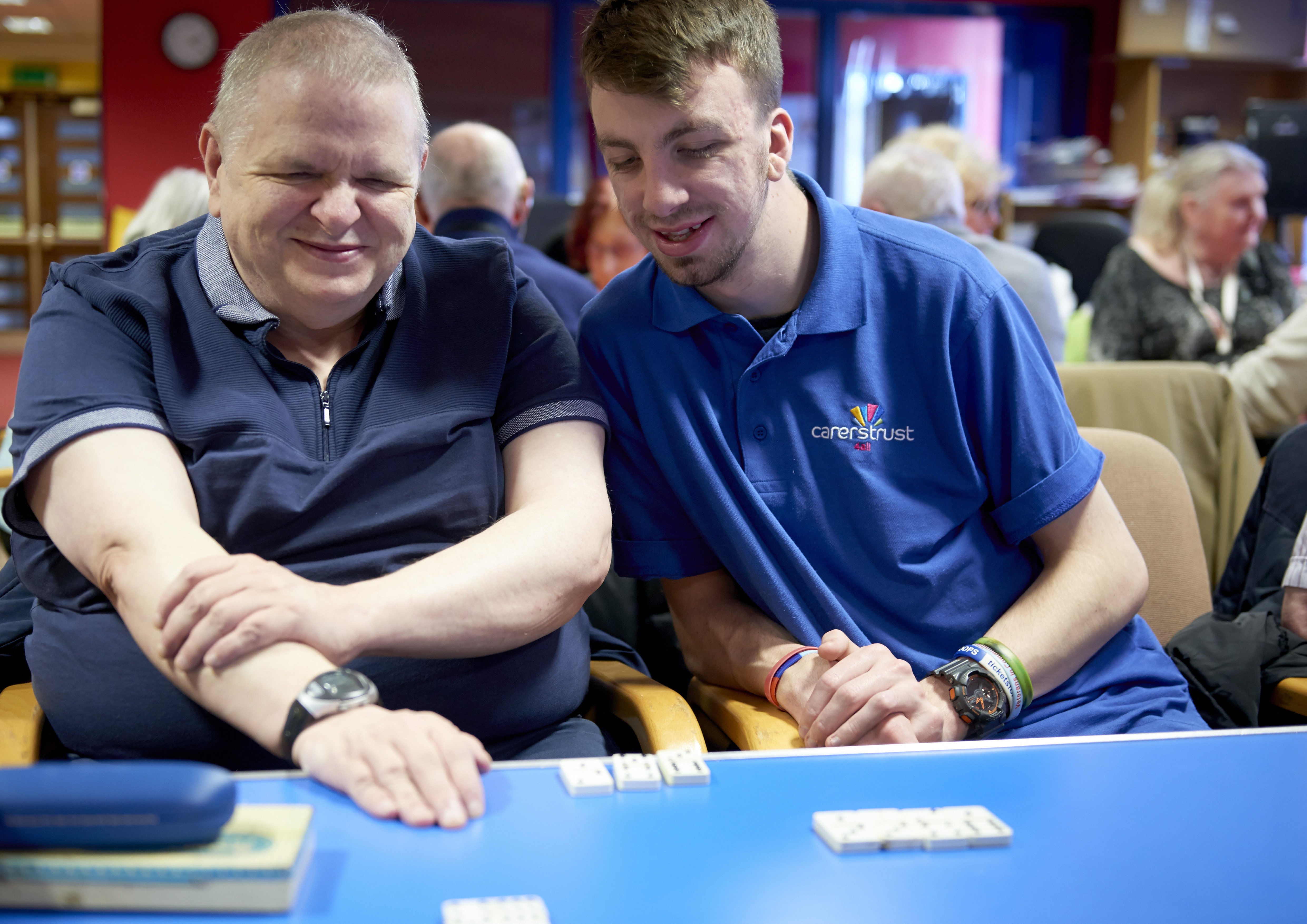 Two young men looking down as they play dominoes in the Trafford hub.