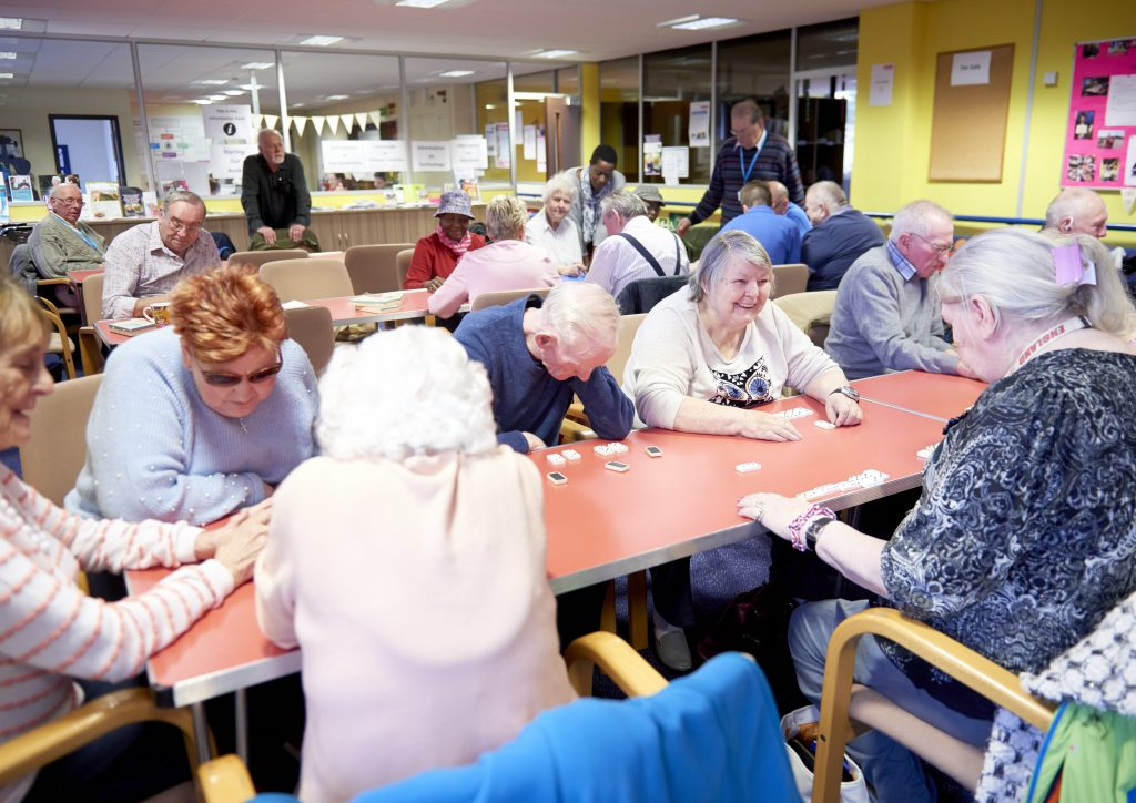 A brightly coloured room with two rows of tables with people playing dominoes.