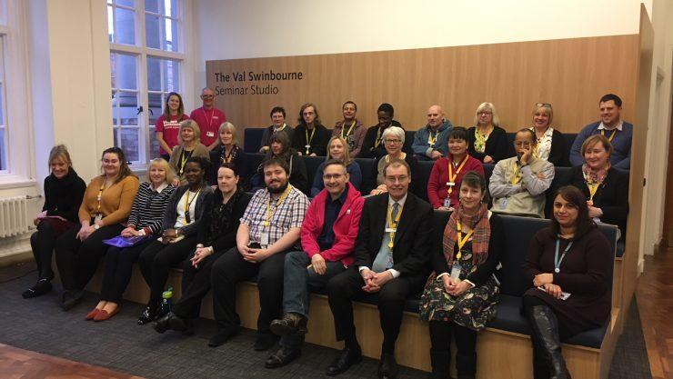 Group photo of Henshaws staff and Manchester Libraries staff sitting together in rows, smiling at the camera.