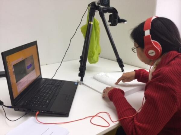 """Henshaws Group Member, MaiLing Wong exploring the 3D print of """"The Kiss"""" by Klimt with audio information and description."""