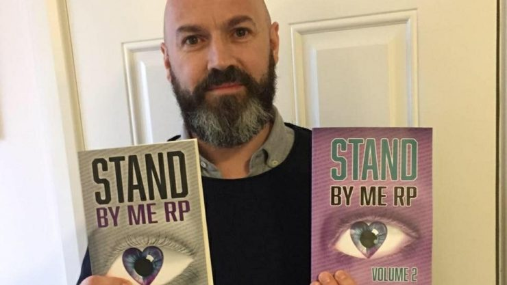 Dave holding a copy of two of his books, smiling at the camera.