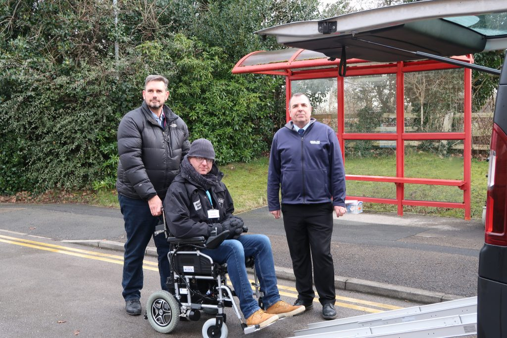A person in a wheelchair being pushed up a transport ramp into a taxi as part of a mobility training programme