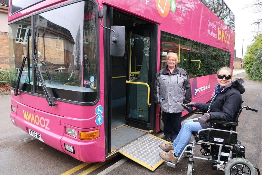 A lady in a powered wheelchair boarding a bus via a ramp, looked on by the lady bus driver