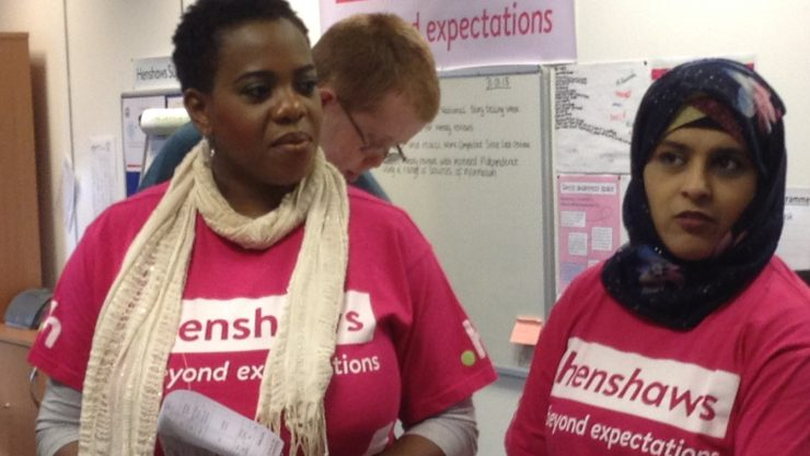 Two female staff wearing pink Henshaws t-shirts at an open event