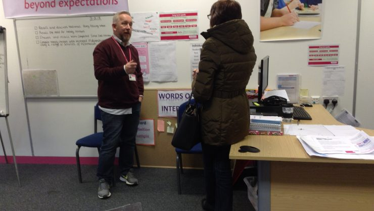 Male Henshaws staff member speaking to a lady in an office setting