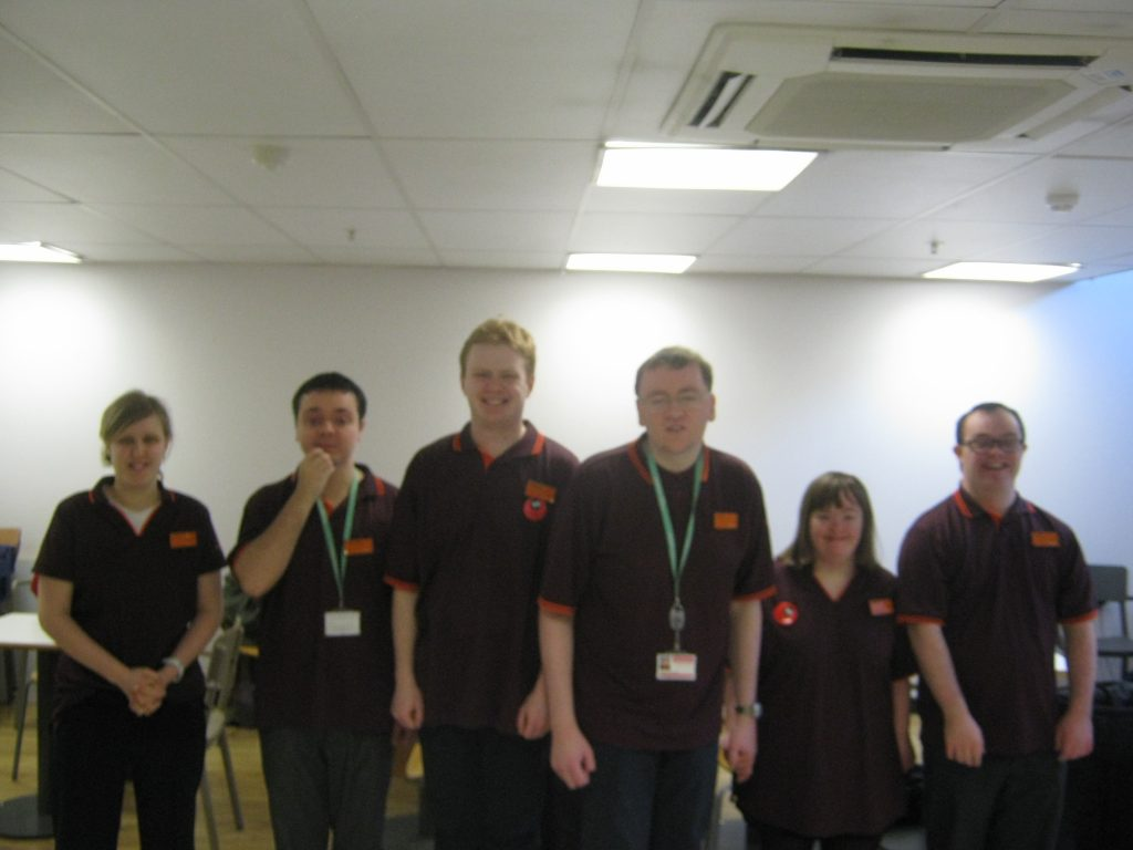 A group of six students smiling at the camera wearing their Sainsburys uniforms.