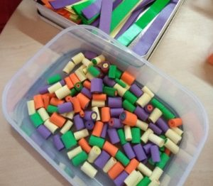 A box containing strips of coloured paper and another box full of brightly coloured paper beads