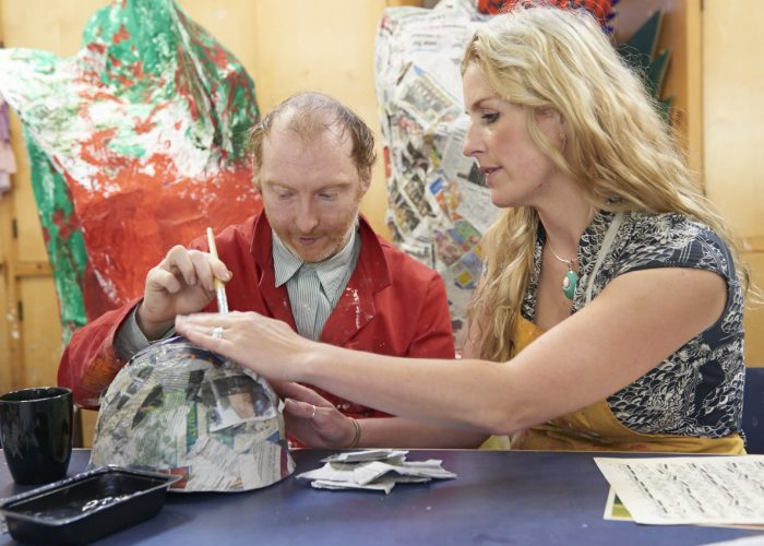 A man with VI makes a papier mache model with support from a female workshop leader