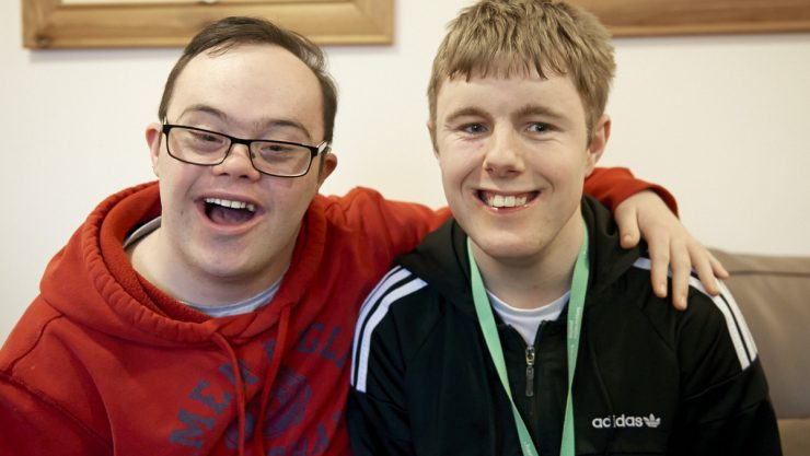Two young adult males from a specialist college sat together and smiling