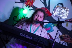 A VI student sat at a piano playing and singing in a talent competition
