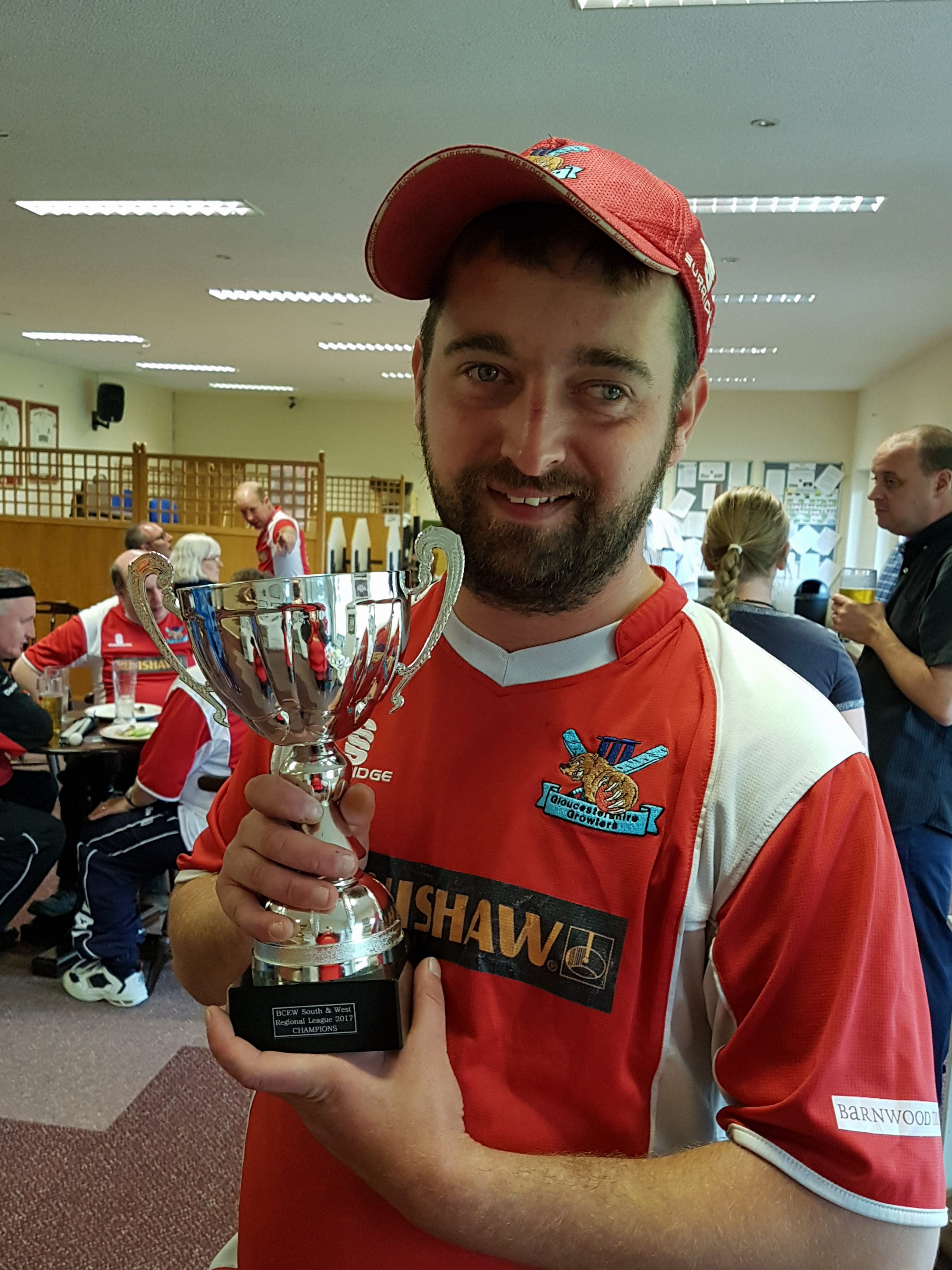 Marc in a red shirt and cap posing with his trophy in front of a bar.