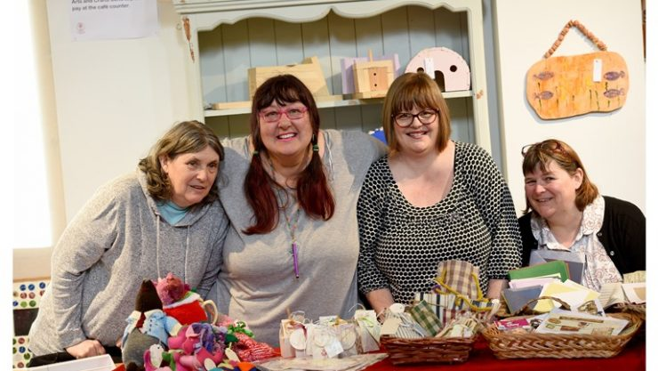 A group of four female volunteers at a craft fair stall