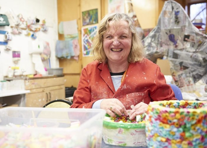 A lady with a visual impairment seated at a table and making paper craft out of colourful pieces of paper