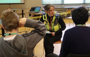 A female police community support officer chats to two young people all seated