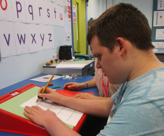 A male student is writing a story using a pencil and paper on a sloped support