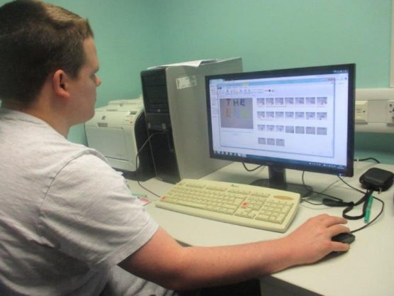 A male student sits at a computer using the mouse