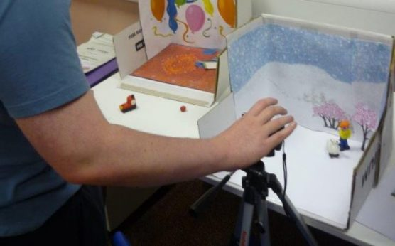 A hand point a camera on a tripod at a scene created using a cardboard box to make an animated film